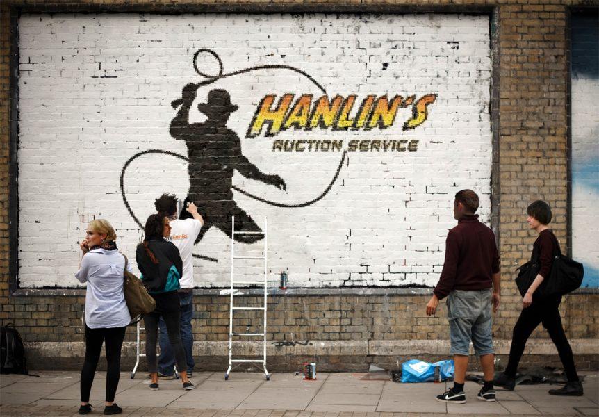 Logo Hanlinovy aukční služby: plný obrys postavy s bičem - patrně Indiana Jones