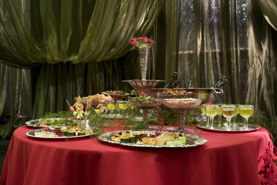 Na stole s červeným ubrusem je vyskládané jídlo na stříbrných podnosech. Uprostřed je váza s květinou.