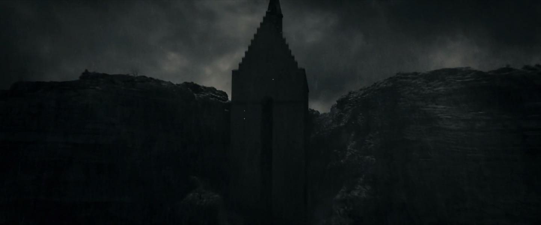 Urpsotřed temné fotografie je strohá věžovitá stavba. Kolem ní tmavé hory a tmavě šedá mračna.