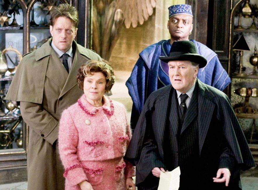 Scéna z filmu Harry Potter a Fénixův řád, ve které se nacházejí 4 osoby: Vlevo nejmenovaný zaměstnanec Ministerstva kouzel, vedle něj Kingsley Pastorek. Před nimi prof. Umbridgeová v tradiční růžové a Popletal v černém obleku a černou buřinkou.