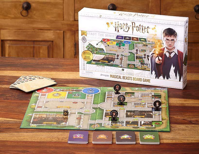 V pozadí je z větší části bílá krabice deskové hry Harry Potter: Kouzelní tvorové. Před ní jsou na dřevěném stole rozloženy herní deska s rozmístěnými figurkami, přehledové tabulky a karty ve čtyřech hromádkách.
