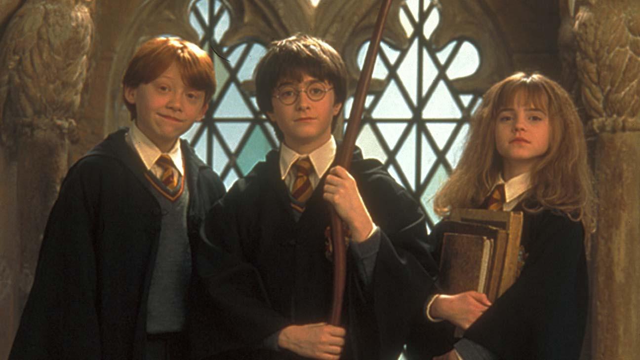 Fotografie Harryho, Rona a Hermiony. Harry stojí uprostřed s koštětem v rukách, Ron po jeho pravé straně (na obrázku vlevo) a Hermiona s knížkami v náručí na jeho levé straně.