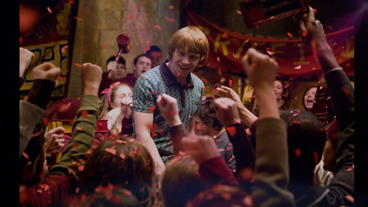 Fotografie scény oslavy v nebelvírské společenské místnosti po vyhraném famfrpálovém zápasu. Je na něm množství lidí se zdviženýma rukama. Nad nimi je usmívající se Ron, který se dívá na skandující Nebelvíry. Ve vzduchu se vznášejí červené konfety.