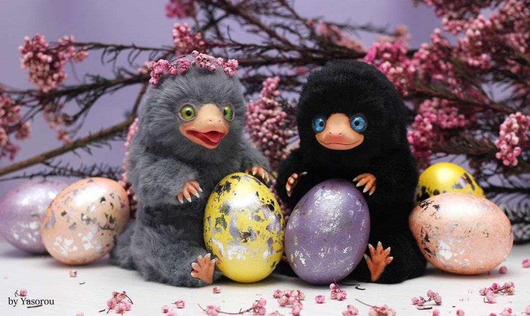 Na fotografii jsou uprostřed dvě ručně vyrobená mláďata hrabáků. Vlevo sedí šedě zbarvené mládě se zeleným očima a před ním je žlutě zbarvené vajíčko se stříbrným zdobení. Vpravo sedí černý hrabáček s modrýma očima a před ním je fialově zbarvené vajíčko se stříbrným zdobením. Na pozadí jsou další fialová, žlutá a růžová vejce se stříbrným zdobením a osušené větvičky s růžovými kvítky.