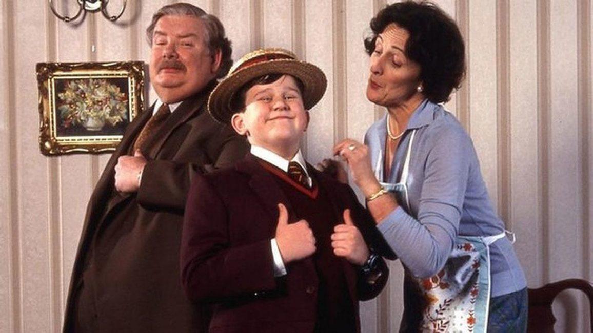 Na fotografii je spokojená rodinka Dursleyových. Úplně vlevo je Vernon v kravatě a v kabátu. Vedle je stejně oblečený malý Dudley se slaměným kloboukem na hlavě a se zdviženými palci rukou. Vpravo je Petunie oblečená v modrém a bílé zástěře, která se s cukrovým výrazem ve tváři dívá na Dudleyho. Fotografie je pořízená v interiéru s tapetami.