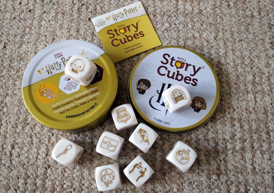 """Na fotografii se světle okrový pozadím je otevřená plechová krabička ve tvaru kruhu. Vlevo je spodní díl krabičky, horní třetina je bílá s logem """"Harry Potter"""" a pod logem je ze dvou třetin zlatá. Vedle vpravo je svrchní díl krabičky v bílé barvě, lemovaný zlatou barvou. Úplně nahoře je logo """"Rory's Story Cubes"""", pod ním logo """"Hp"""" se zlatonkou. Vedle vlevo je chibi Harry a vpravo chibi Hermiona. Na obou usech krabičky jsou bílé kostky a také pod nimi. Mají zlaté obrázky. Nad krabičkou je mezi oběma díly mini letáček."""