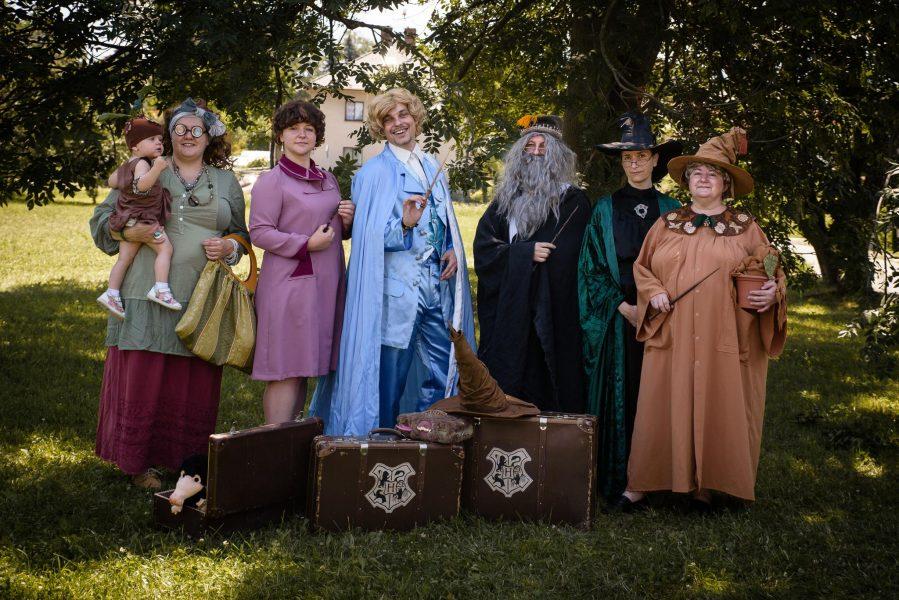 Na fotografii je šest bradavických učitelů, resp. cosplayerů z týmu Potterfan. Zleva profesorka Trelawneyová, držící ve své pravé ruce dítě převlečné za mandragoru. Vedle ní profesorka Umbridgeová, dále Zlatoslav Lockhart v modrém hábitu, Albus Brumbál v černém, profesorka McGonagallová a Pomona Prýtová. V pozadí jsou stromy a před cosplayery tři kufry, z nichž dva více vpravo mají bradavický znak.