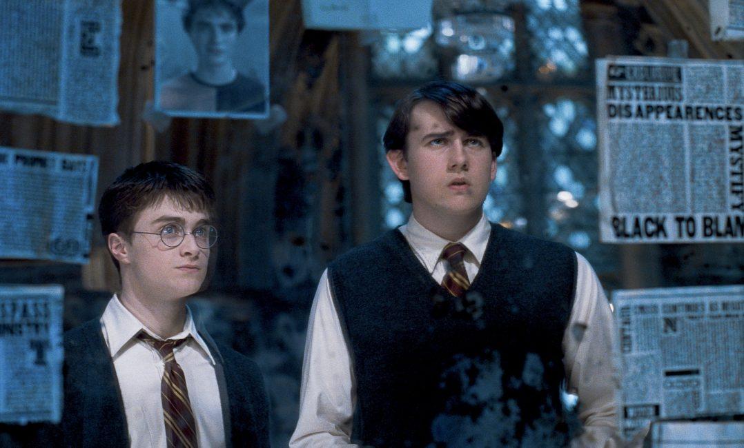 Scéna z filmu Fénixův řád: Harry a Neville stojí před zrcadlem, na němž jsou novinové ústřižky o činnostech Smrtijedů a fotka Cedrika Digorryho.