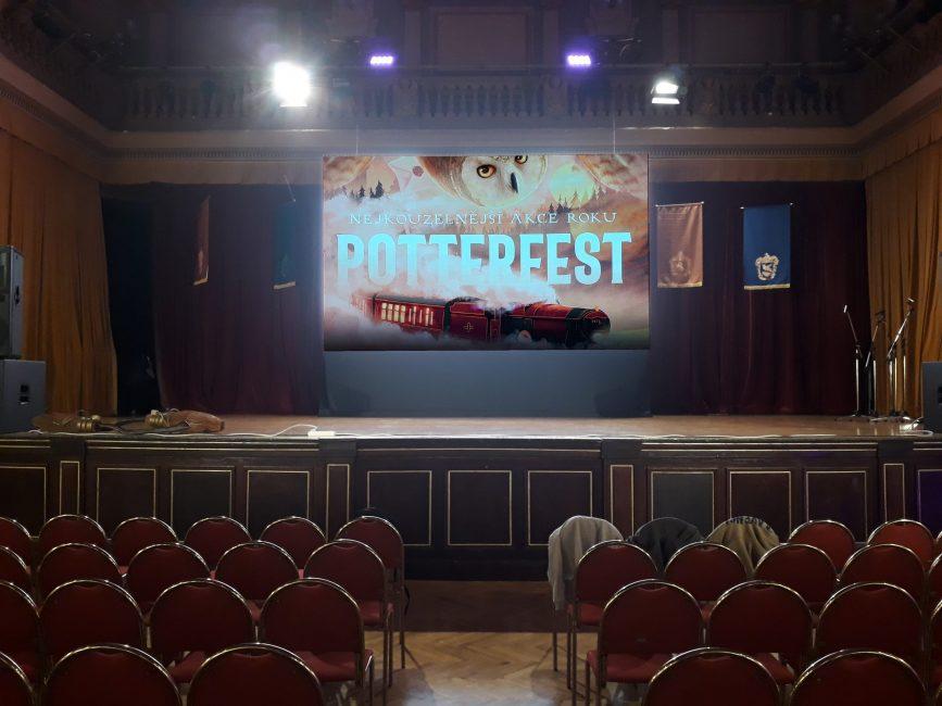 Fotografie z Potterfestu 2021 zobrazující jeviště hlavního sálu. Na zdi za jevištěm visí kolejní prapory, uprostřed je promítací plocha, na které je promítáno logo Potterfestu 2021 (s Hedvikou a bradavickým expresem). Na kraji jeviště jsou položena 2 košťata Nimbus 2000.